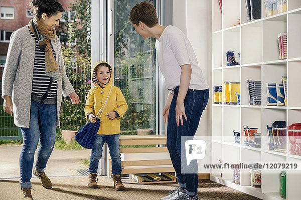 Glücklicher Junge im Regenmantel mit Mutter und Erzieherin im Kindergarten
