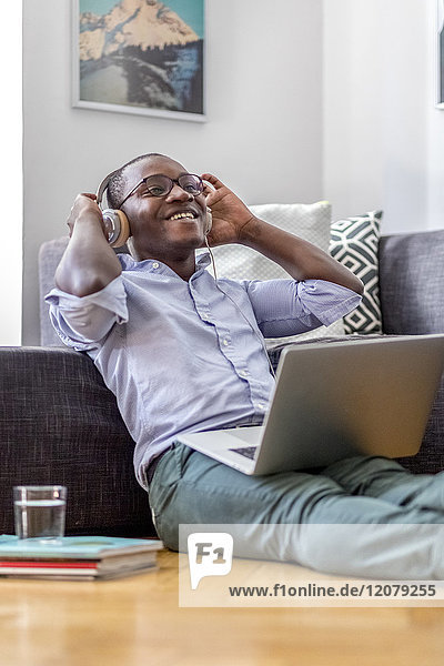 Happy young man sitting on the floor in the living room using laptop and headphones
