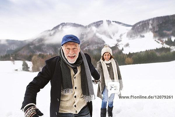 Porträt eines älteren Mannes  der Hand in Hand mit seiner Frau in schneebedeckter Landschaft geht