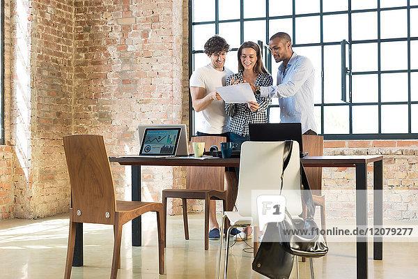 Junge Berufstätige  die in einem Start-up-Unternehmen zusammenarbeiten und einen Businessplan entwickeln.