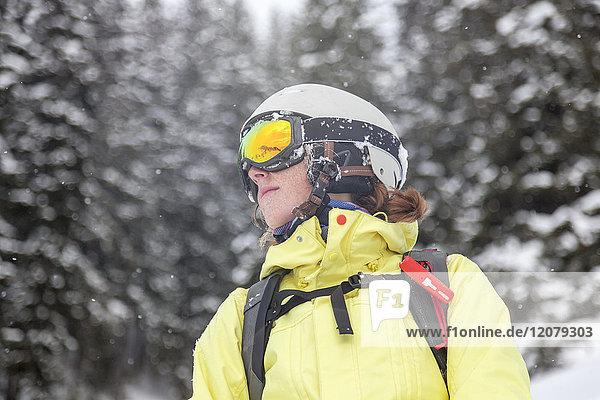 Österreich  Kitzbühel  Frau mit Skihelm und Lawinenrucksack im Schnee