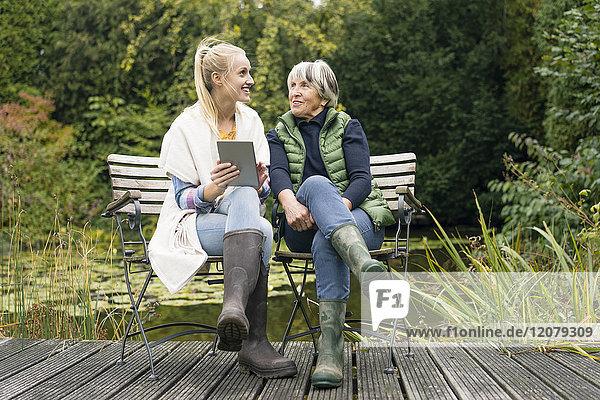 Lächelnde junge Frau mit ihrer Großmutter auf dem Steg am Gartenteich.
