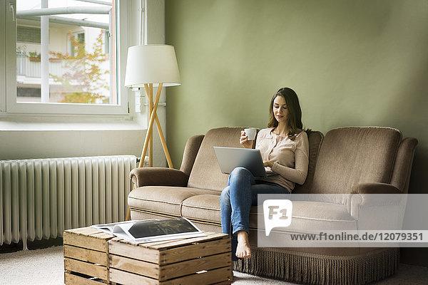 Junge Frau sitzend auf der Couch mit Tasse Kaffee mit Laptop