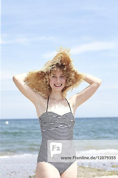 Porträt einer lachenden jungen Frau mit Strohhut am Strand