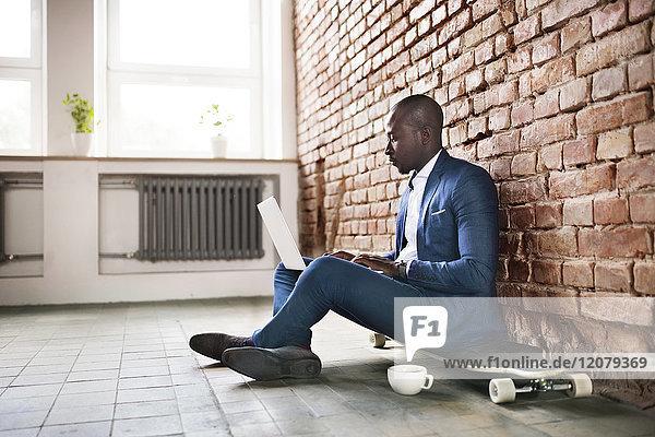 Geschäftsmann auf Longboard an der Ziegelwand sitzend mit Laptop