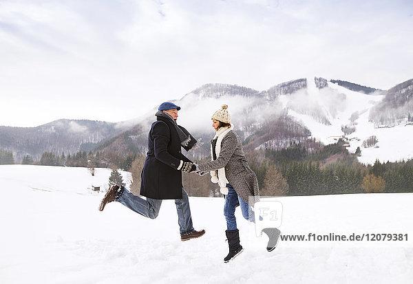 Glückliches Seniorenpaar beim Springen in der Luft in verschneiter Landschaft