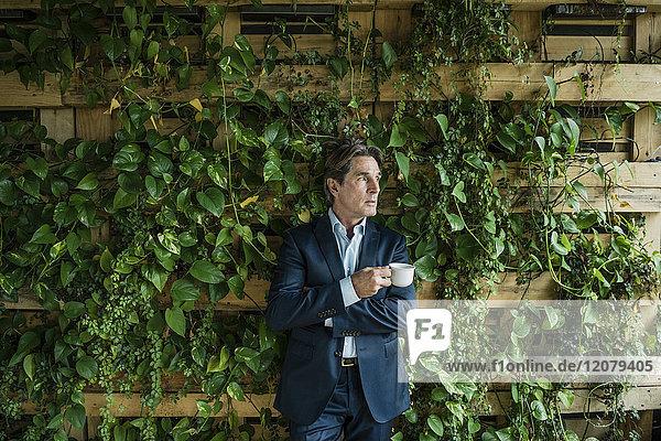 Geschäftsmann mit Tasse Kaffee im grünen Büro