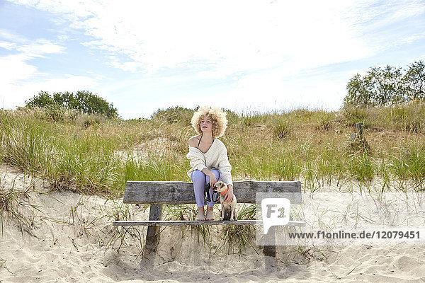 Junge Frau sitzt auf einer Bank in den Dünen und ihr Hund schaut in die Ferne.