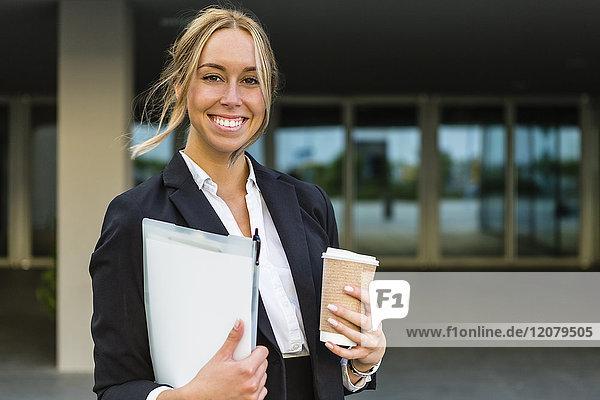 Portrait einer glücklichen Geschäftsfrau mit Dokumenten und Kaffee zum Mitnehmen