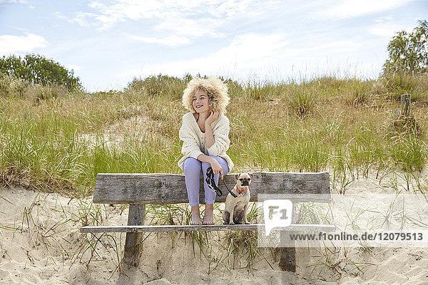 Porträt einer glücklichen jungen Frau  die mit ihrem Hund auf einer Bank in den Dünen sitzt.