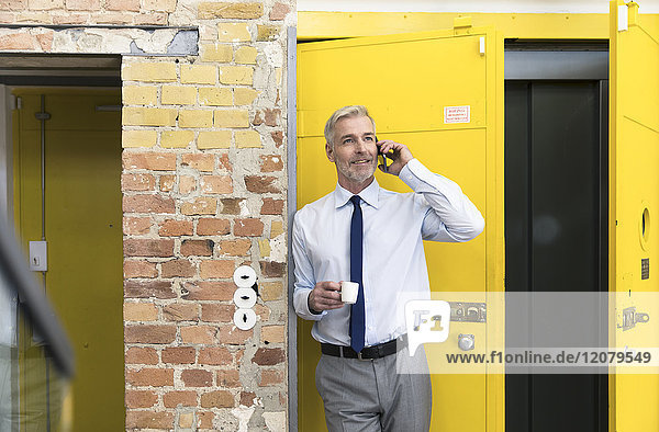 Geschäftsmann lehnt sich mit dem Smartphone vor den Aufzug und trinkt Kaffee.