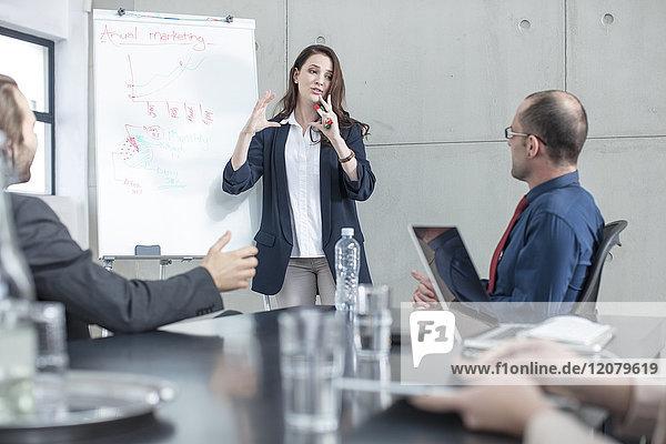 Geschäftsfrau  die eine Präsentation über eine Besprechung im Konferenzraum leitet