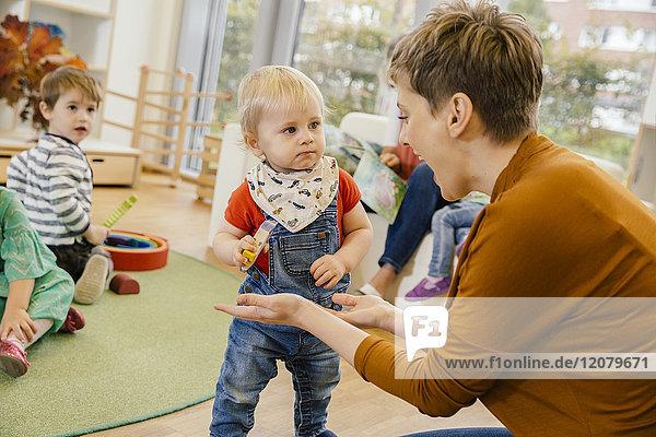 Vorschullehrer beim Spielen mit dem kleinen Jungen im Kindergarten