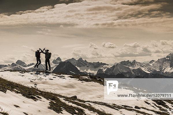 Deutschland  Bayern  Oberstdorf  zwei Wanderer beim Springen in alpiner Landschaft