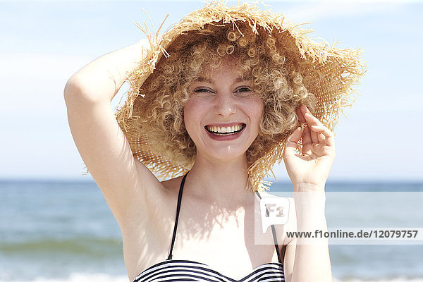 Portrait of laughing young woman wearing straw hat on the beach
