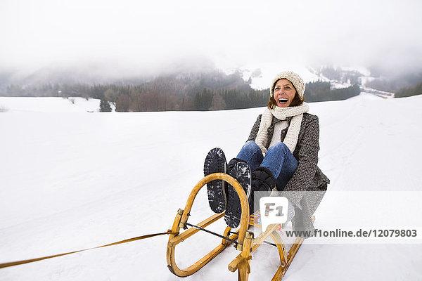 Lachende Seniorenfrau auf Schlitten in verschneiter Landschaft