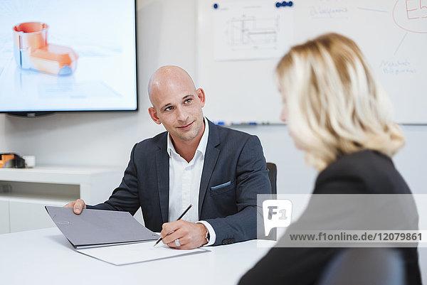 Geschäftsmann und Geschäftsfrau im Gespräch im Büro