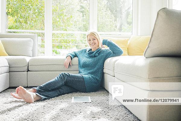 Porträt einer lächelnden Frau  die sich im Wohnzimmer entspannt.