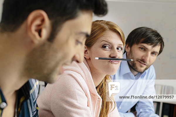 Portrait of playful young woman with colleagues in office