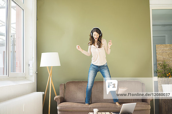 Young woman with headphones standing on couch screaming and dancing