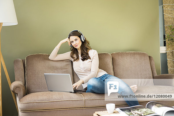 Young woman with headphones sitting on couch using laptop