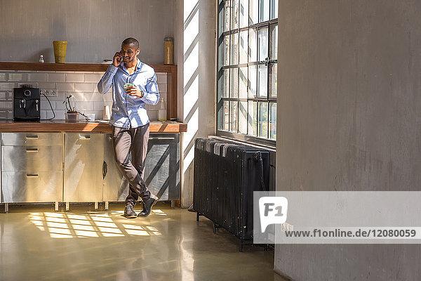 Jungunternehmer steht in der Firmenküche  trinkt Kaffee  nutzt Smartphone