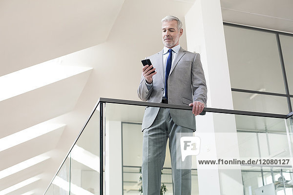 Geschäftsmann im Büro mit seinem Handy