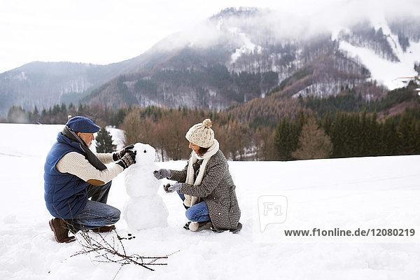 Seniorenpaar baut Schneemann in Winterlandschaft auf