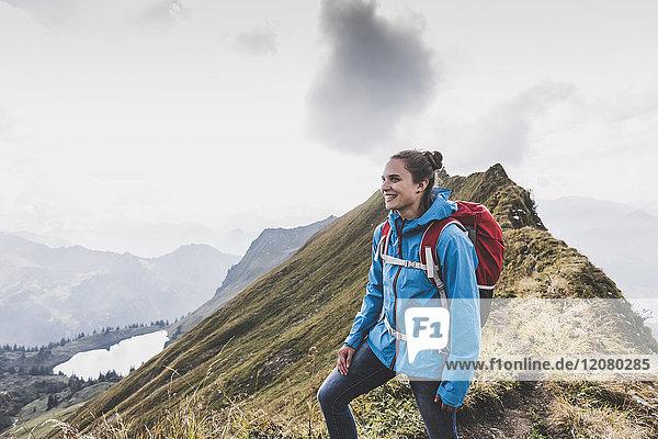 Deutschland  Bayern  Oberstdorf  lächelnde Frau auf dem Bergrücken stehend