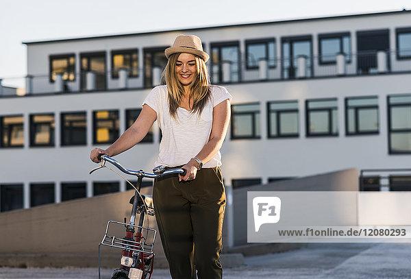 Lächelnde junge Frau mit Fahrrad auf Parkebene