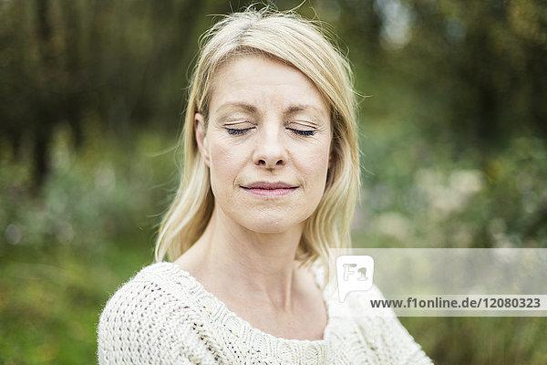 Porträt einer blonden Frau mit geschlossenen Augen im Freien