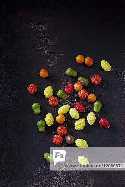 Kaugummis in Form von Früchten auf dunklem Grund