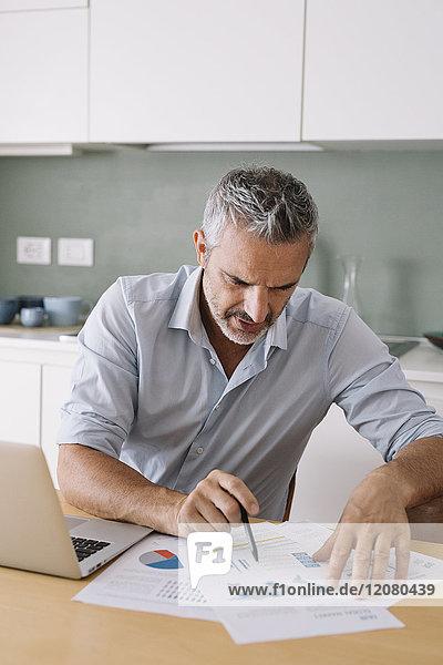 Mann analysiert Daten und nutzt Laptop im Home-Office