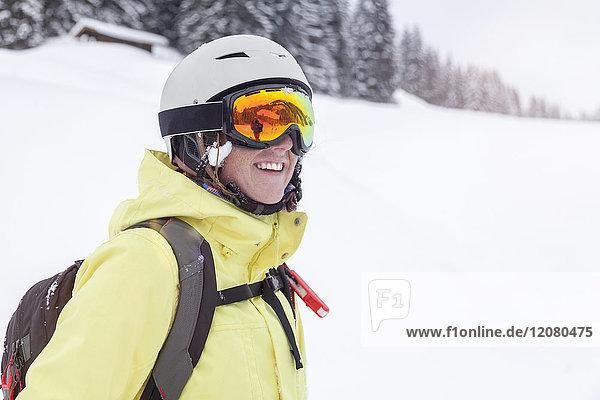 Österreich  Kitzbühel  lächelnde Frau mit Skihelm und Lawinenrucksack in den Bergen