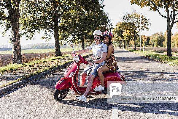 Porträt des glücklichen jungen Paares auf dem Motorroller auf der Landstraße