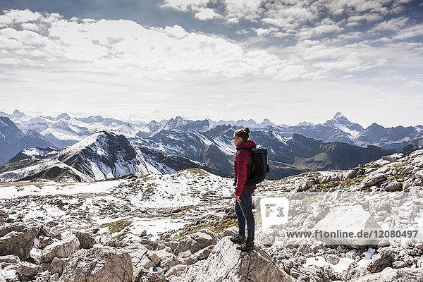 Deutschland  Bayern  Oberstdorf  Frau auf Felsen stehend in alpiner Landschaft