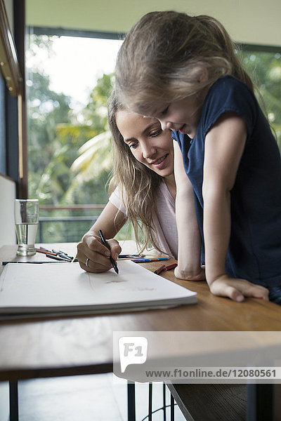 Mutter und Tochter zeichnen mit Buntstiften