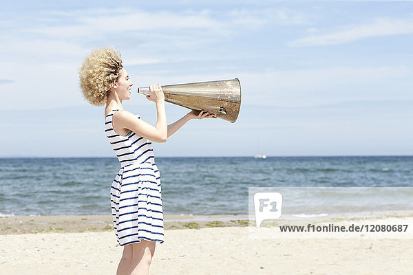 Junge Frau mit Megaphon am Strand