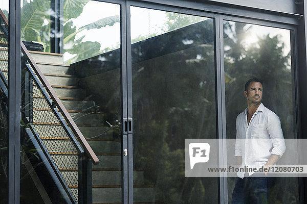 Der reife Mann steht in seinem modernen Haus und schaut durchs Fenster.