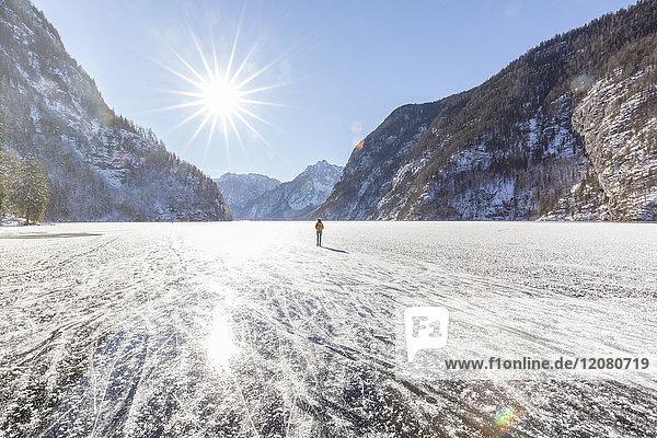 Deutschland  Berchtesgadener Land  Rückansicht der Frau mit Rucksack am gefrorenen Königssee