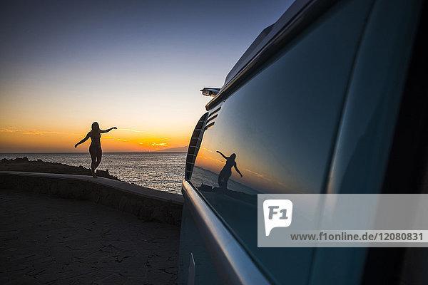 Silhouette einer Frau  die bei Sonnenuntergang an der Wand vor dem Meer balanciert.