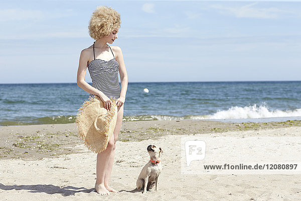 Young woman in swimsuit with straw hat and dog on the beach