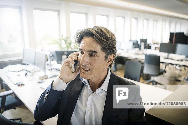 Geschäftsmann im Büro am Handy