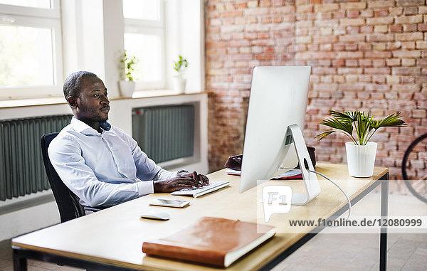 Geschäftsmann mit Computer am Schreibtisch im Büro
