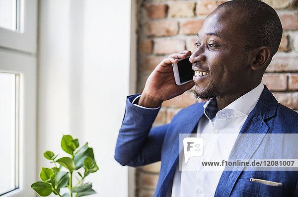 Smiling businessman on cell phone at the window
