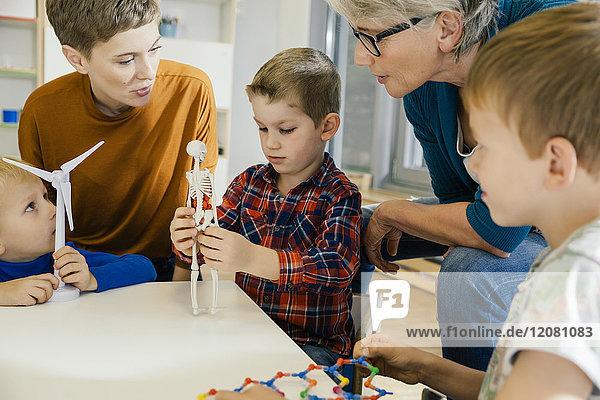 Kinder und Vorschullehrer mit Windkraftanlage und Anatomiemodell im Kindergarten
