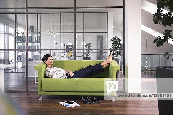 Geschäftsfrau beim Mittagsschlaf auf der Couch im Büro
