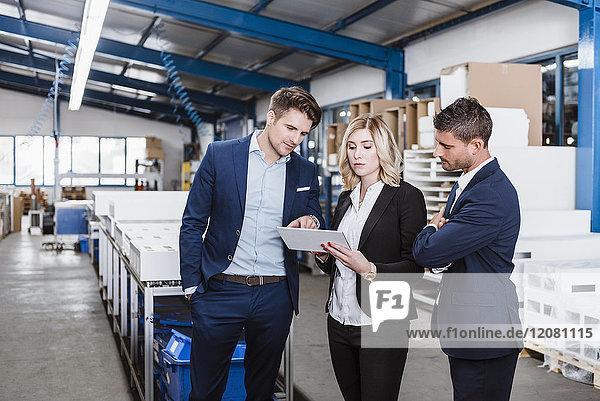 Drei Geschäftsleute diskutieren in der Werkstatt mit Hilfe eines digitalen Tabletts.