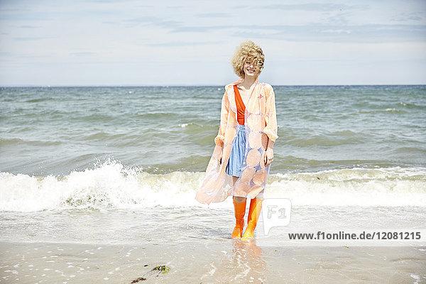 Lächelnde junge Frau in Regenmantel und Wellington-Stiefeln am Meer stehend