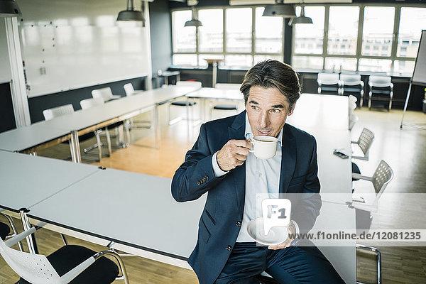 Geschäftsmann mit Tasse Kaffee auf dem Tisch im Besprechungsraum eines Büros